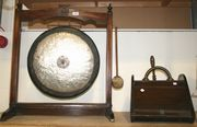 An Edwardian gong on an oak stand, together with a coal scuttle.