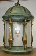 A brass, verdigris metal and glass ceiling light of cylindrical form with dome top.