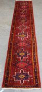 A Hamadan runner, North-west Persia, late 20th Century, the red field with hooked medallions and guls, within a blue complimentary border, approx 370cm x 72cm.