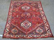 A Hamadan rug, North-west Persia, 20th Century, the red field with three stepped medallions, within an ivory and leaf border, approx 168cm x 122cm.