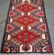 A Hamadan rug, North-west Persia, modern, the ivory field with three linked medallions supported by polychrome guls, within a thin blue and claret border, approx 148cm x 82cm.