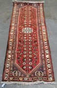 A Hamadan runner, North-west Persia, 20th Century, the red field with ivory lobed medallions and an ascending flowering vine, within an ivory border, approx 198cm x 69cm.