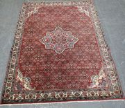 A Tabriz rug, North-west Persia, mid-20th Century, the red field with a lobed foliate medallion supported by overall herati, within an ivory palmette and flowering vine border, approx 165cm x 116cm.