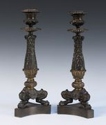 A pair of Regency brown and gilt patinated cast bronze candlesticks, each circular sconce above an acanthus leaf stem, raised on tripod legs with claw feet, united by a triform base, height approx 33.5cm.