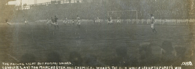A photographic postcard of a football match in progress titled 'The Failing Light but Pompey Shines, Lovely (Clay)ton Manchester and Chemical Works the Kick which led up to Pompey's Win', published by Cribb