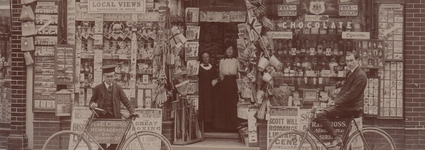 A photographic postcard of R. & E. Cross Newsagents and Confectioners shopfront with extensive postcard display and employees outside the Surrey Street shop in Littlehampto