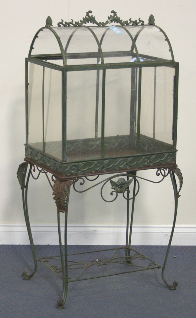 A Green Patinated Wrought Metal Conservatory Terrarium With Domed Lid Raised On Acanthus Leaf Adorn