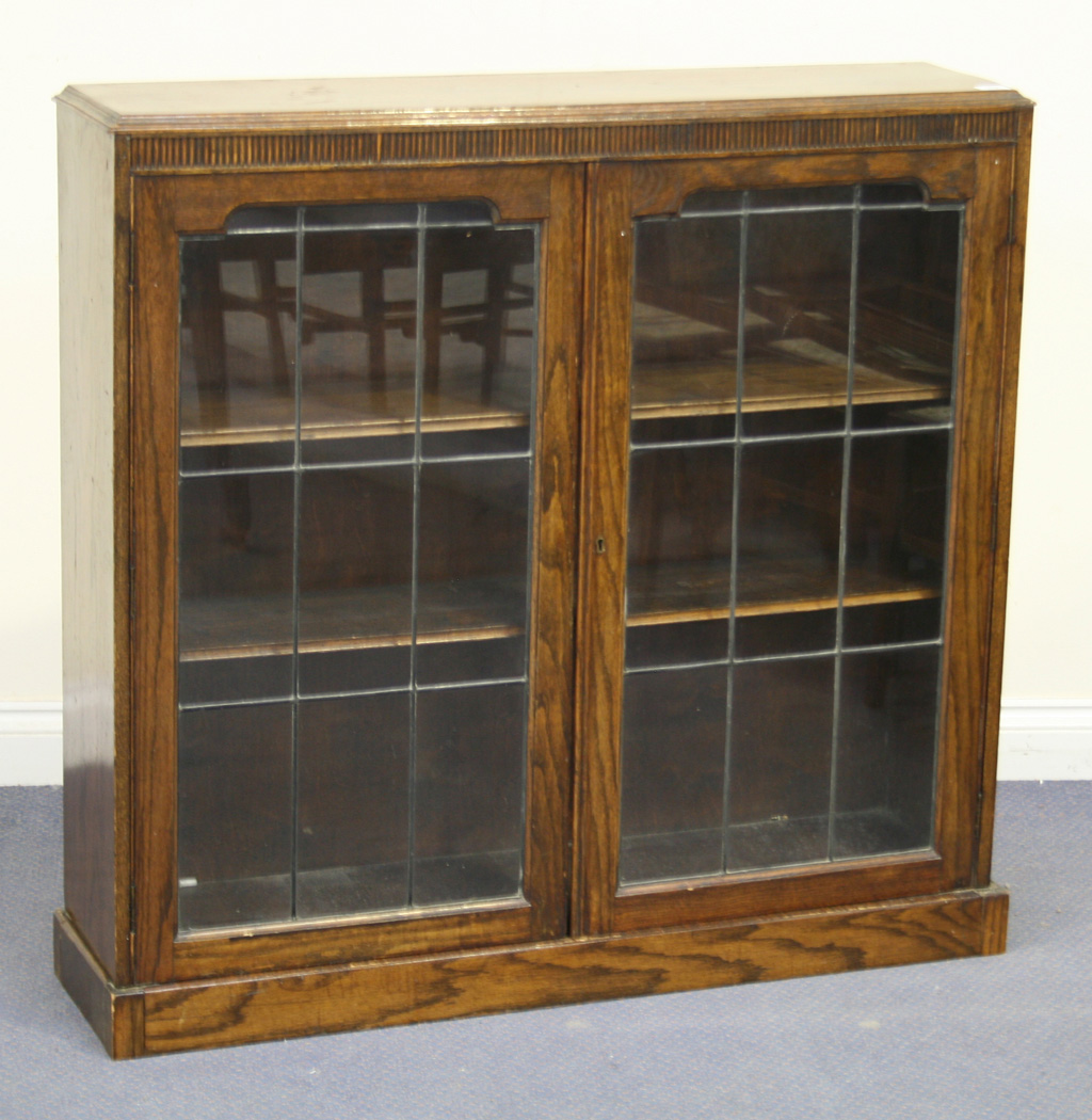 A George V Oak Bookcase Fitted With A Pair Of Leaded Glass