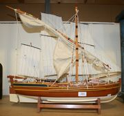 A late 20th Century model of a three-masted sailing boat with half-painted hull, the detailed deck mounted with eight cannons and dinghy, overall length approx 80cm, together with a single-masted sailing and rowing boat with half-painted hull, the detailed deck mounted with three cannons, overall length approx 60cm.
