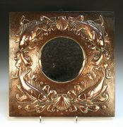 An Arts and Crafts Newlyn copper wall mirror, the tondo bevelled glass mirror within a relief surround of four fish and two scallop shells on a hammered background, stamped 'Newlyn', approx 49cm x 48.5cm.