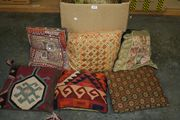 Two Persian carpet covered cushions and a collection of other cushions.
