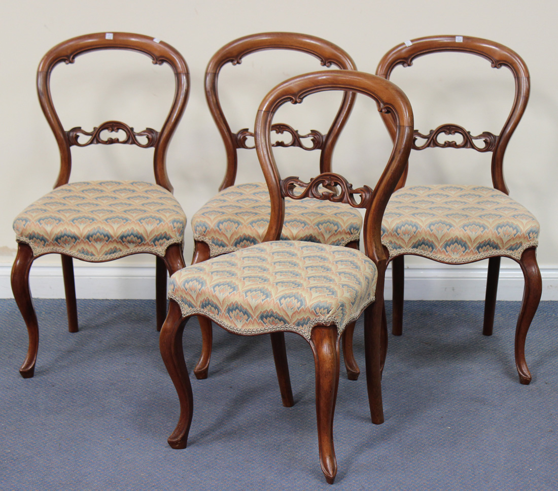 A Set Of Four Victorian Walnut Balloon Back Dining Chairs The Seats Overstuffed On Cabriole Legs