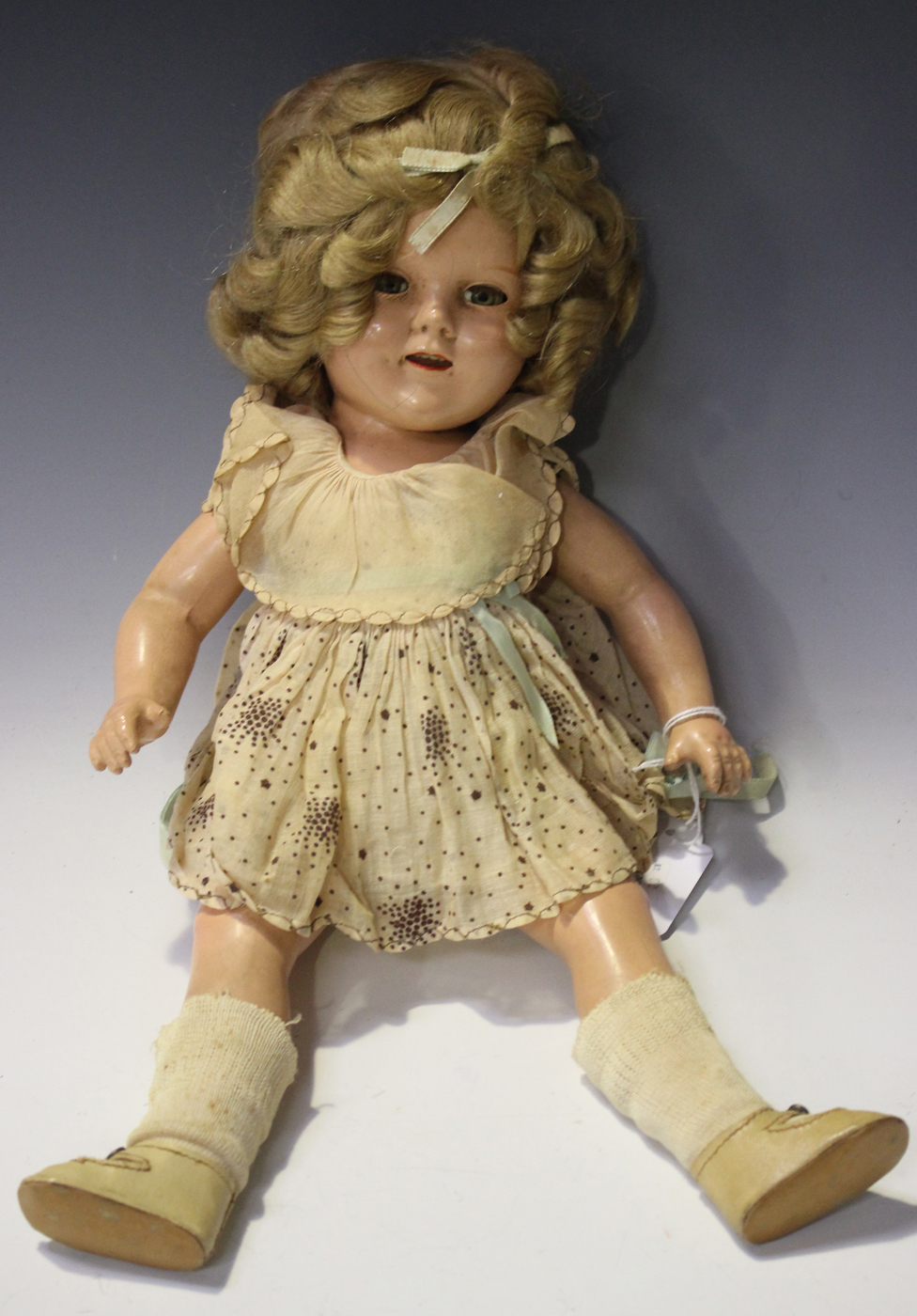 b11a33dc8968 A Shirley Temple composition doll with blonde hair, closing brown eyes,  open mouth showing upper tee