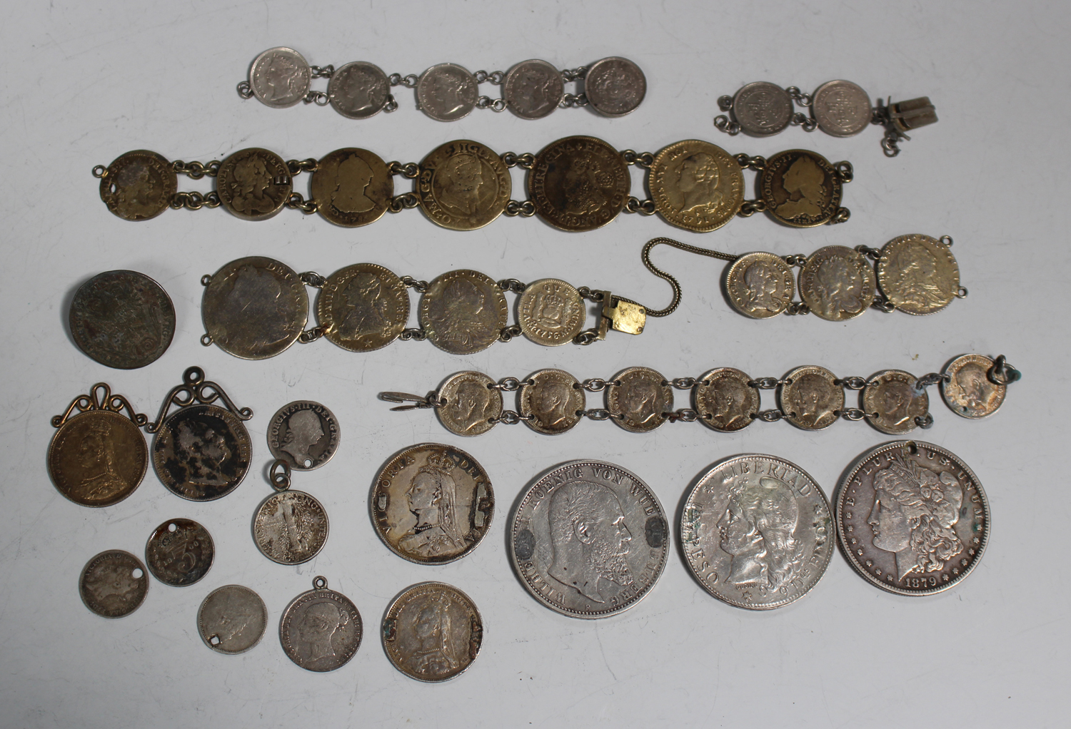 A group of various world coins, all mounted or previously